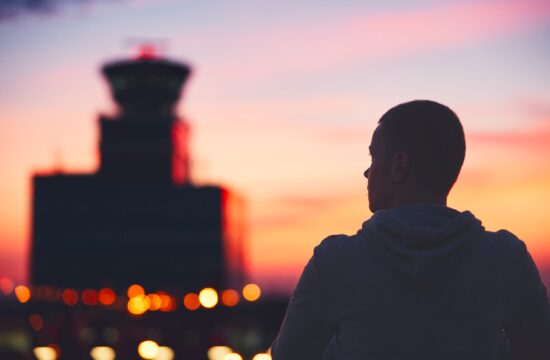 Silhouette of the traveler at the airport. Air Traffic Control Tower at the amazing sunset. Prague, Czech Republic.