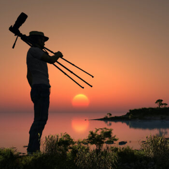 Silhouette of a tourist with a camera on a sunset.